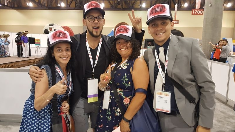 4 smiling people wearing airbrushed trucker caps