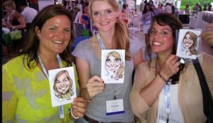 3 smiling ladies hold their lanyard of the digital caricatures they had done of themselves.