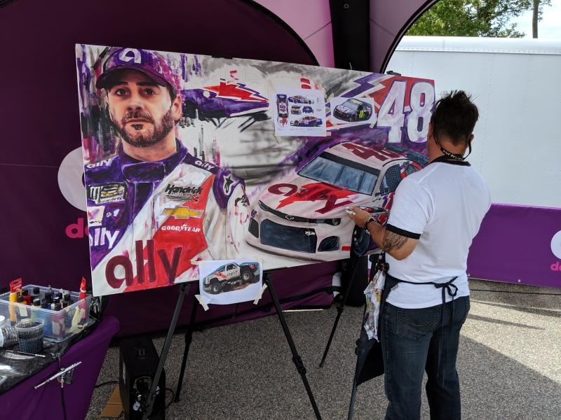 Large canvas being painted of Jimmie Johnson and his race car.