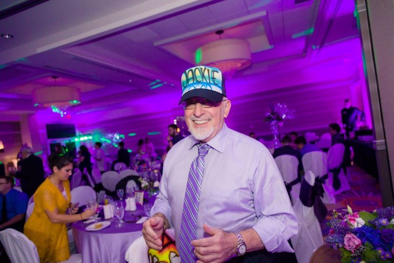 An older man is wearing an airbrush events hat in the middle of a people in a function hall.