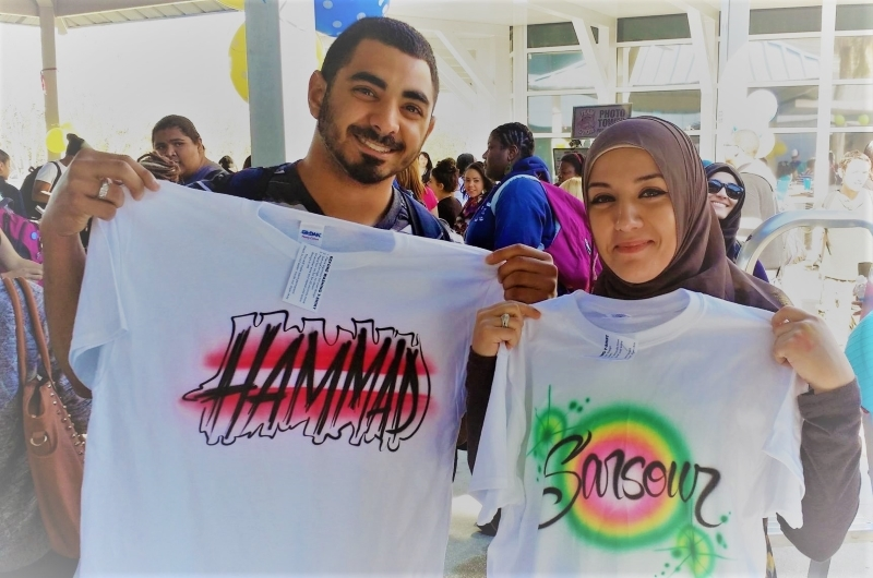 A Muslim woman and a man hold up airbrushed t-shirts they had just had personalized from Airbrush Events