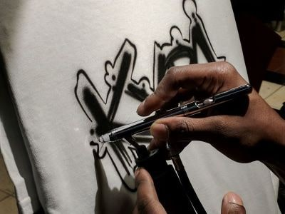 A hand holds an airbrush gun painting block lettering onto a white shirt.