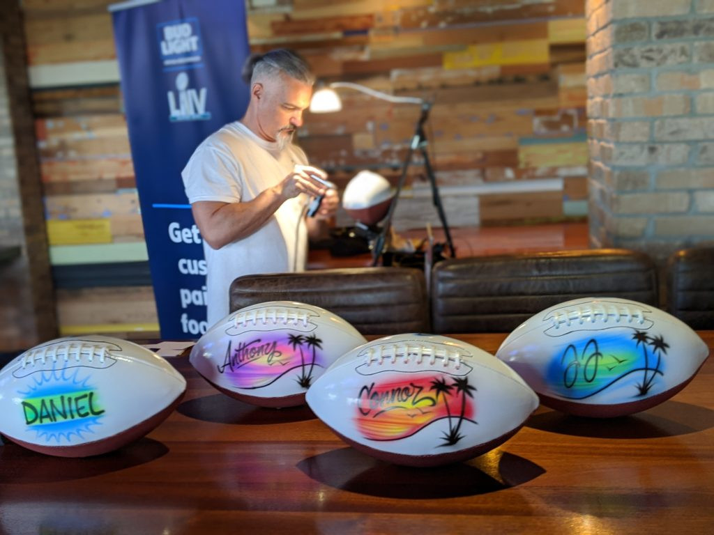 custom airbrushed footballs sit in the foreground while an airbrush artist paints another football in the background