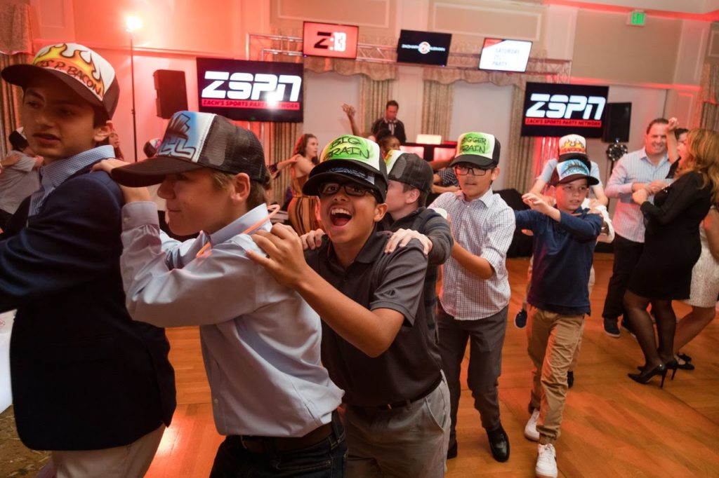 6 boys wearing airbrushed trucker caps make a human train with smiles on their faces.