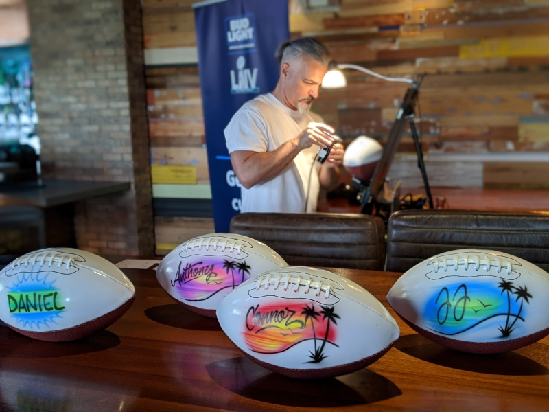 Personalized footballs sit on a wooden table in front of artist at brand activations