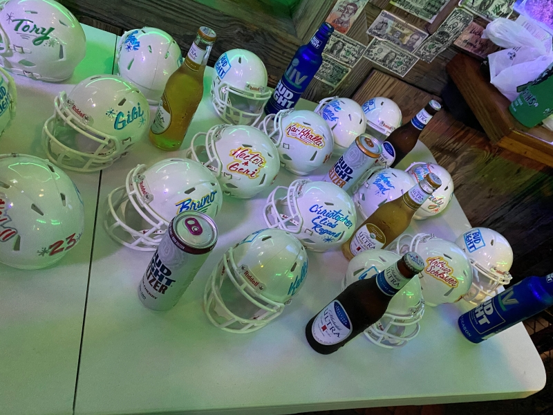 Mini football helmets sit on top of a table with Bud Light products scattered around during the Bud Light brand activations