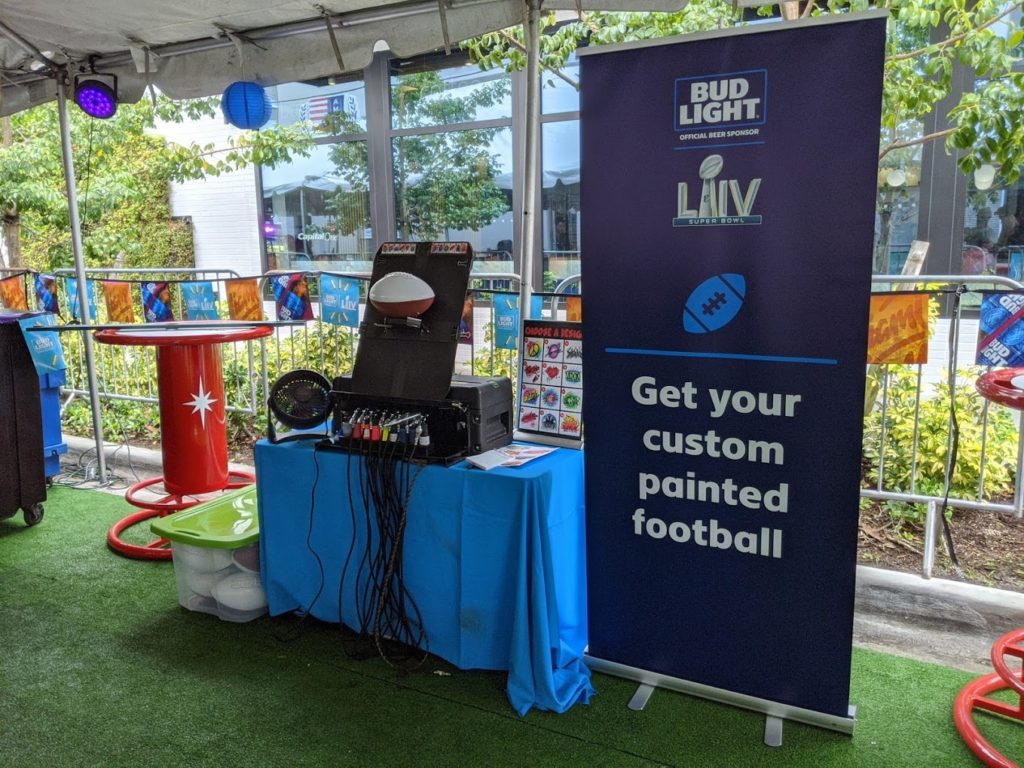 Airbrush Events booth with a banner advertising custom painted footballs during Bud Light activation