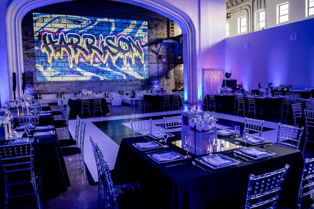 Harrison is written in graffiti-like script on a wall at a bar mitzvah party