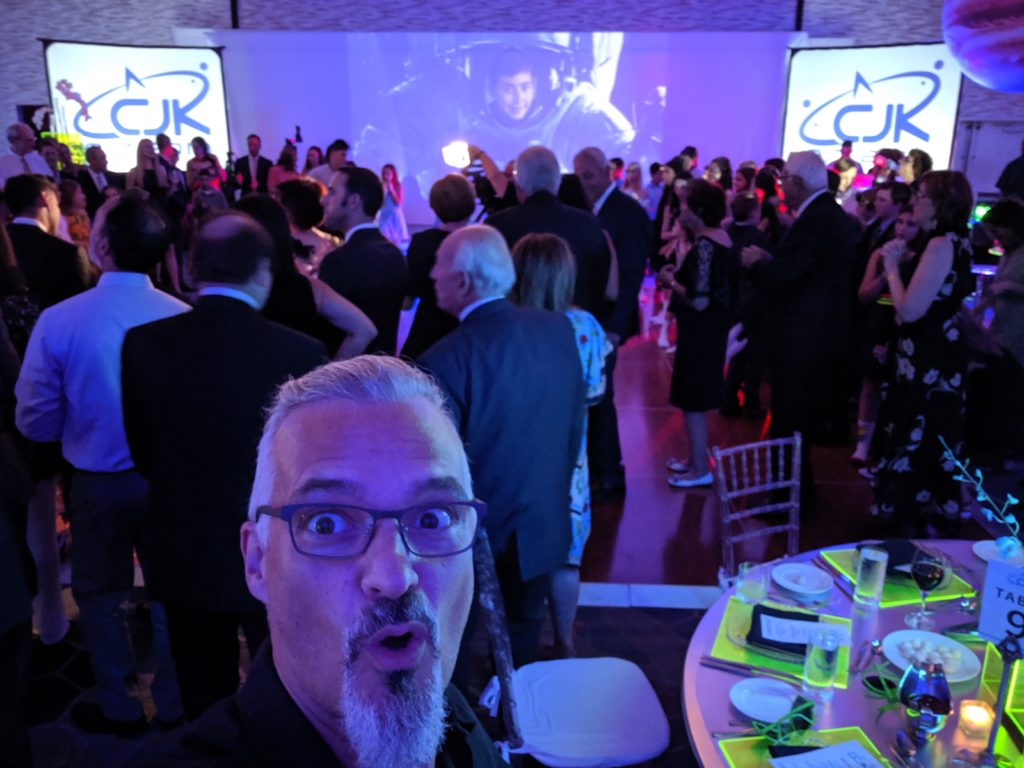 Pete with a shocked look on his face standing in front of a dancing crowd of people at a bat mitzvah