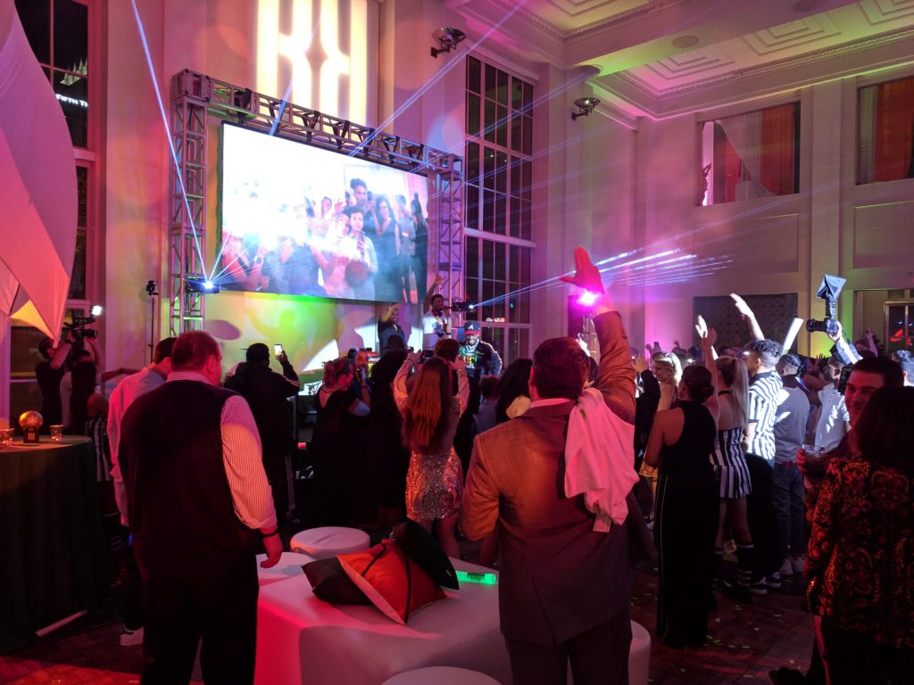 Bar mitzvah guests dance and wave their hands in front of a stage