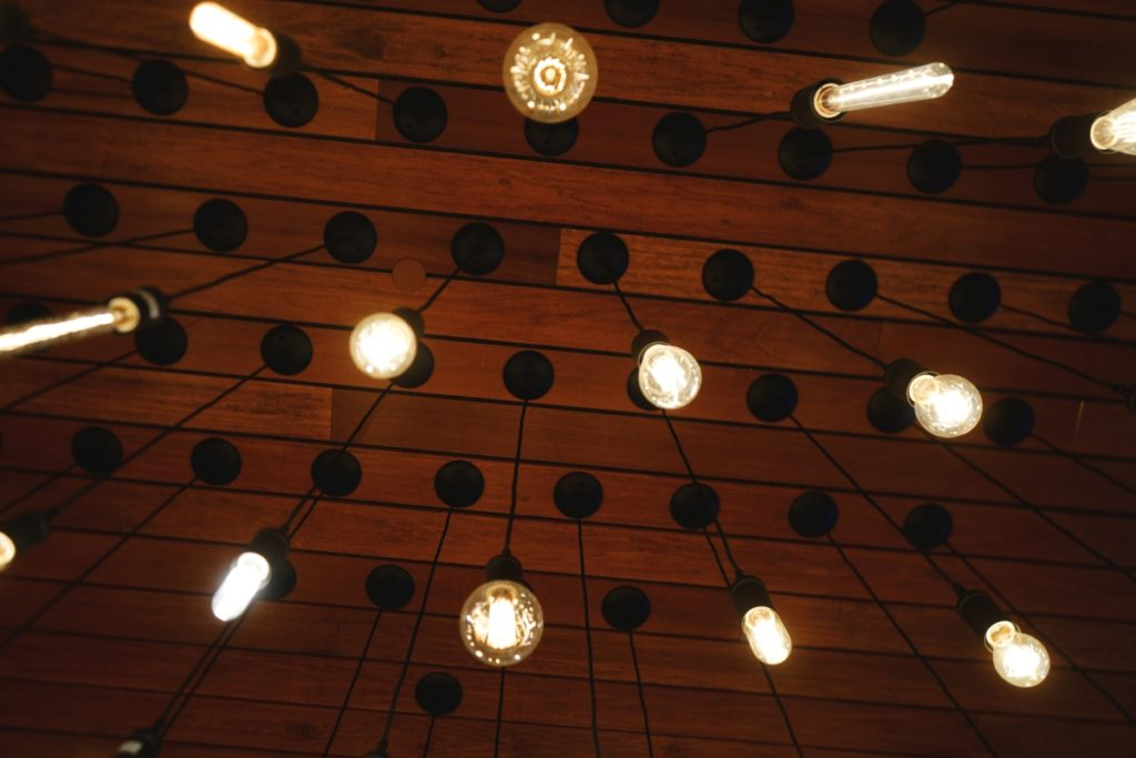 lit light bulbs hang from a ceiling at a bar mitzvah party