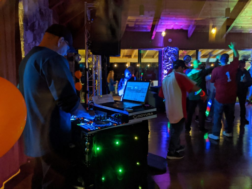A DJ spins the tunes in front of dancing crowd of people at a bar mitzvah party.
