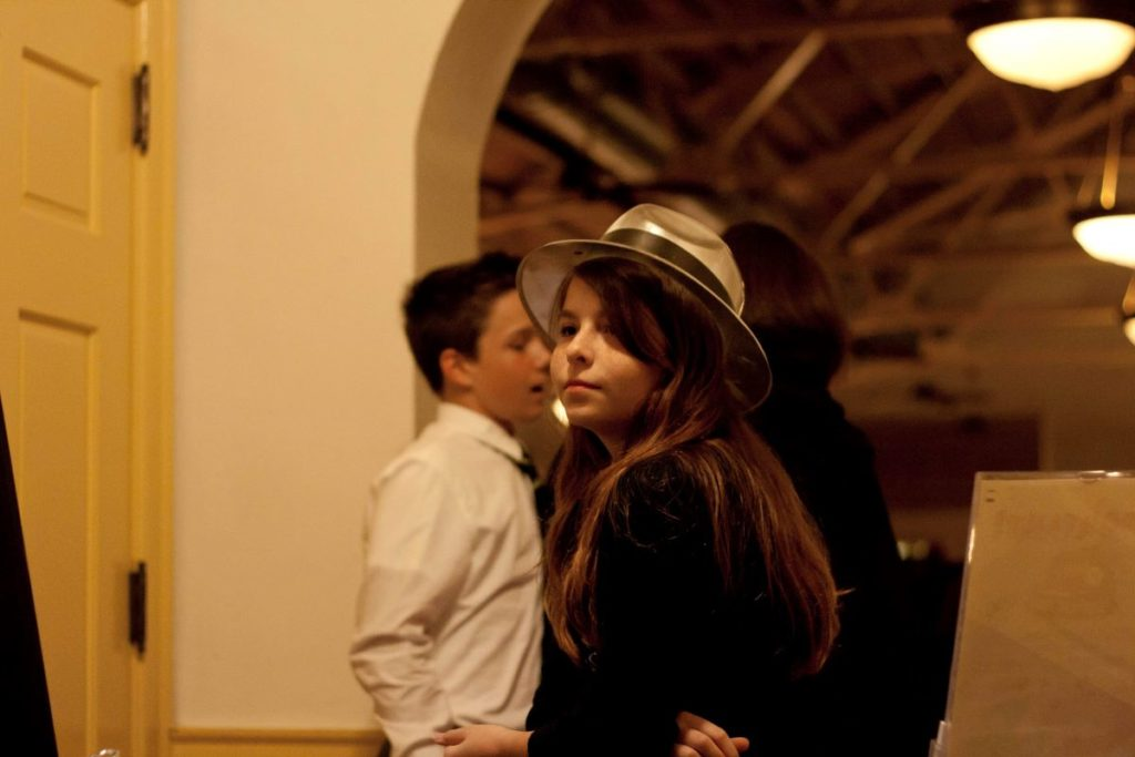 a dark-haired girl wearing a party hat stands in the midst of people