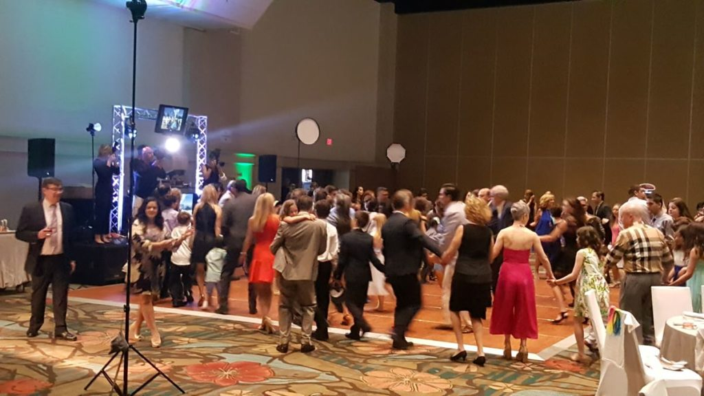 Bar Mitzvah attendees dance in front of a brightly-lit stage