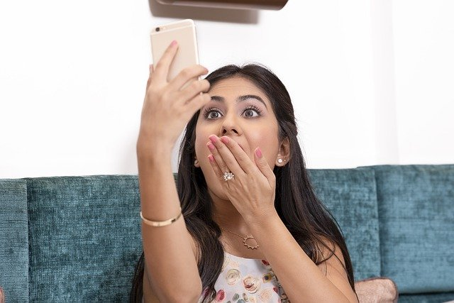 Teen girl stares at her phone in surprise at her fun birthday party while quarantined