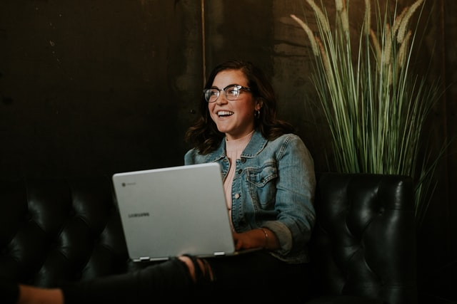 a girl with a jean jacket sits in front of a computer