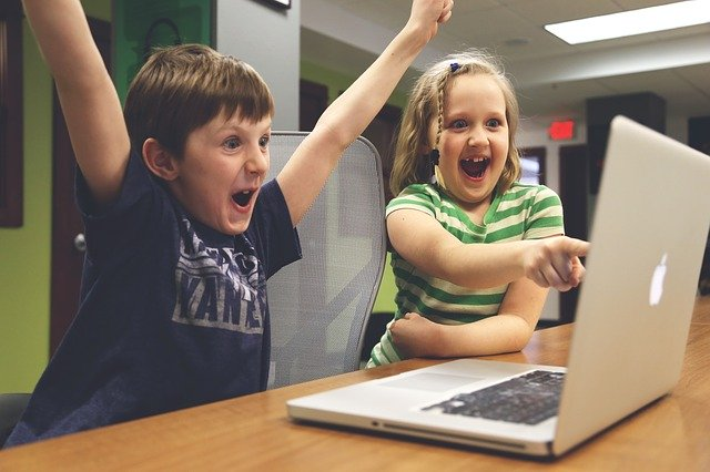 a boy and girl laugh while playing a game on a computer