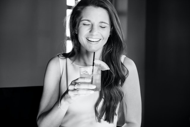 a smiling woman with a cocktail at the virtual cocktail party