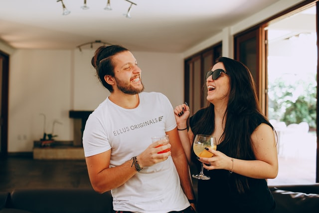 2 people laughing while attending a virtual cocktail party