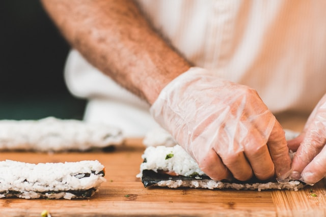 A latex gloved hand prepares sushi
