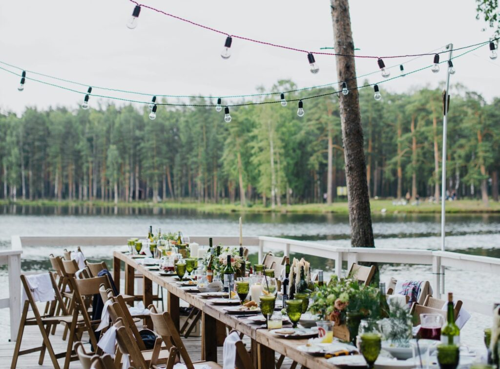 a long wooden table decorated with plants and dishes set in front of a pond